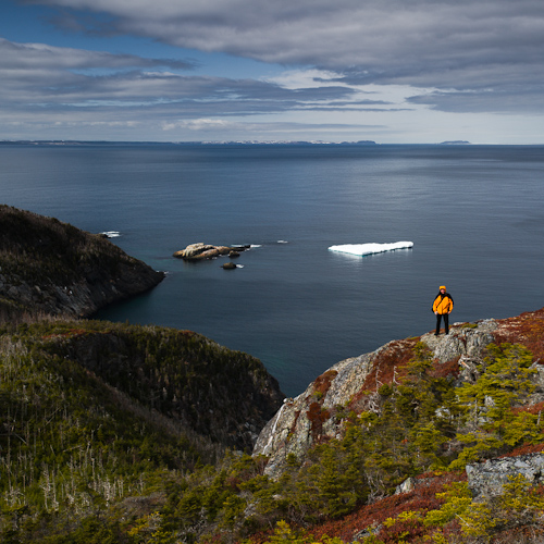 Me on the trail, a small iceberg in the bay - Cripple Cove Path / White Horse Path